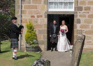 Photo of the Bride and Groom with their Piper